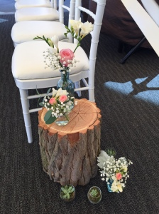 We decorated the aisle with small vases on and around wood stumps
