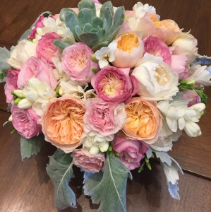 Closeup of lush centerpiece made up of garden roses, succulents, freesia, and dusty miller.